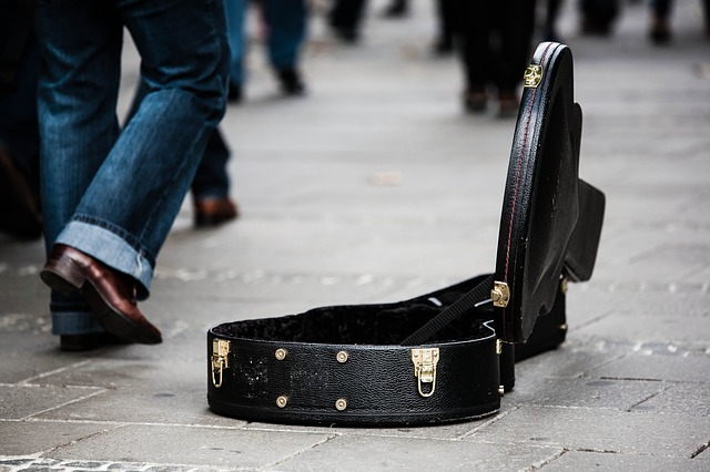 guitar case open on the sidewalk