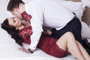 Sexy and elegant couple are kissing in bedroom.