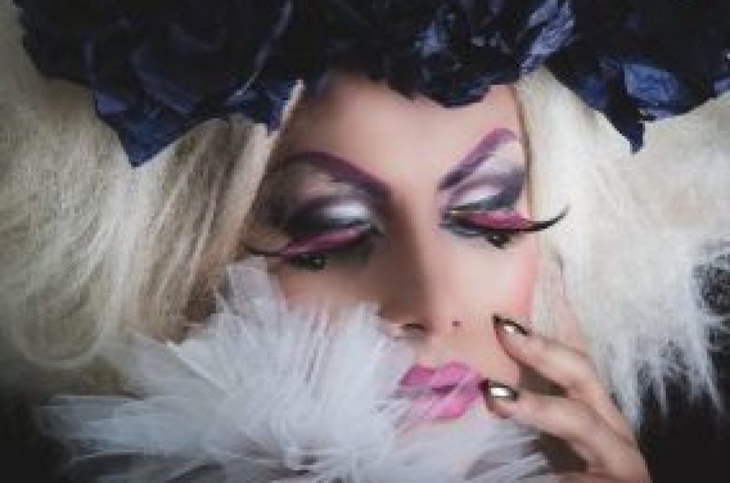 Drag queen with spectacular makeup, glamorous trashy look, posing happily and charming camera from sideways angle.