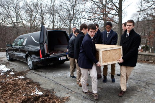 Brendan McInerney (front, from left), Noah Piou, Emmett Dalton and their fellow students from Roxbury Latin boys' school carry the casket of a man who was left unclaimed by family to a grave site in Fairview Cemetery on Friday.