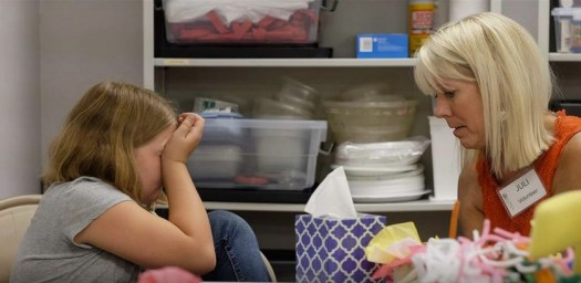 Kela Grooms, 10, who lost her mother to cancer, cries during a group activity with volunteer Julianne Lang
