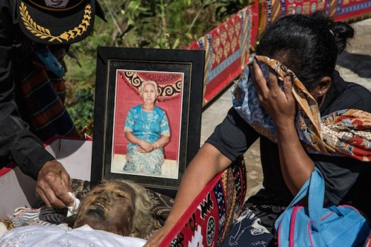 A woman cries in front of the corpse of Marta Ratte Limbong during the Ma'Nene ritual in Ba'Tan Village, Toraja, South Sulawesi, Indonesia. Locals believe dead family members are still with them, even if they died hundreds of years ago.