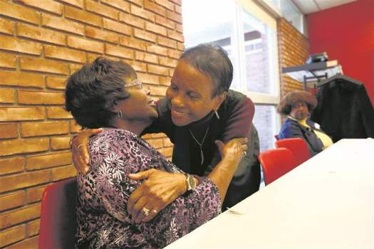 Widows Josephine Cleaves, left, and Aleada Whitehead, right, both of Toledo, hug each other during a support group for widows at Reynolds Corners Library.