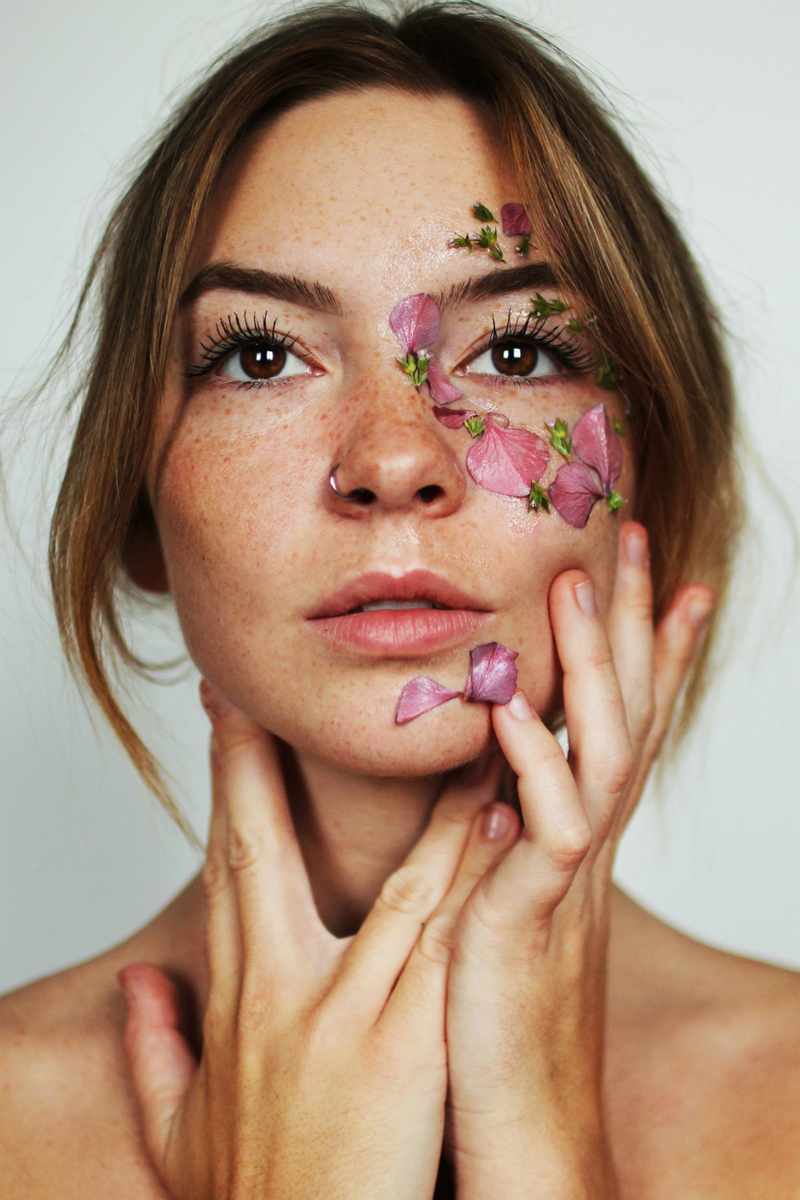 women, with petals on face and hand cupping her cheek and chin