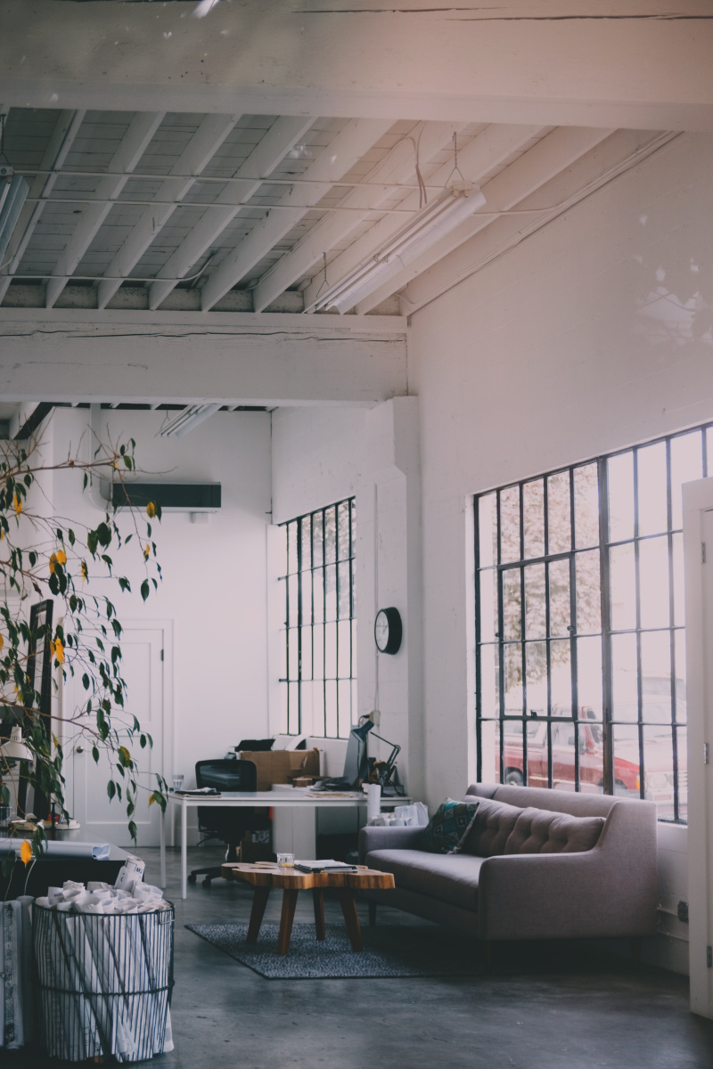 how to decorate your home this year - An image of a washed out room with black crittal windows and sun streaming through and a grey low slung couch