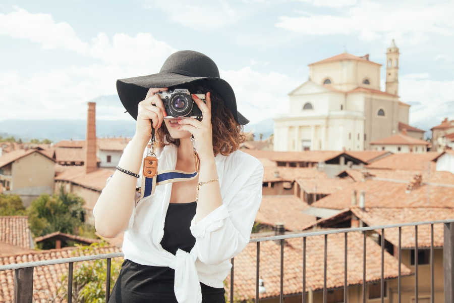 lady taking a photograph with the background of buildings behind her