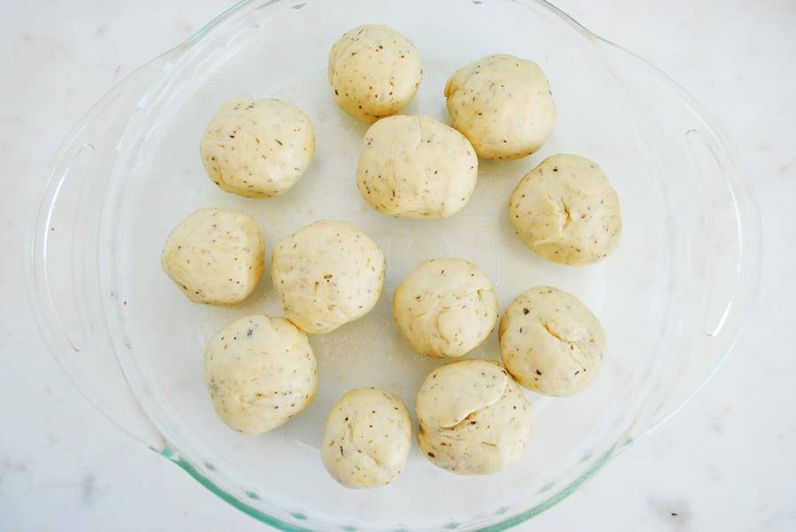 Place the dough balls into a greased round dish.