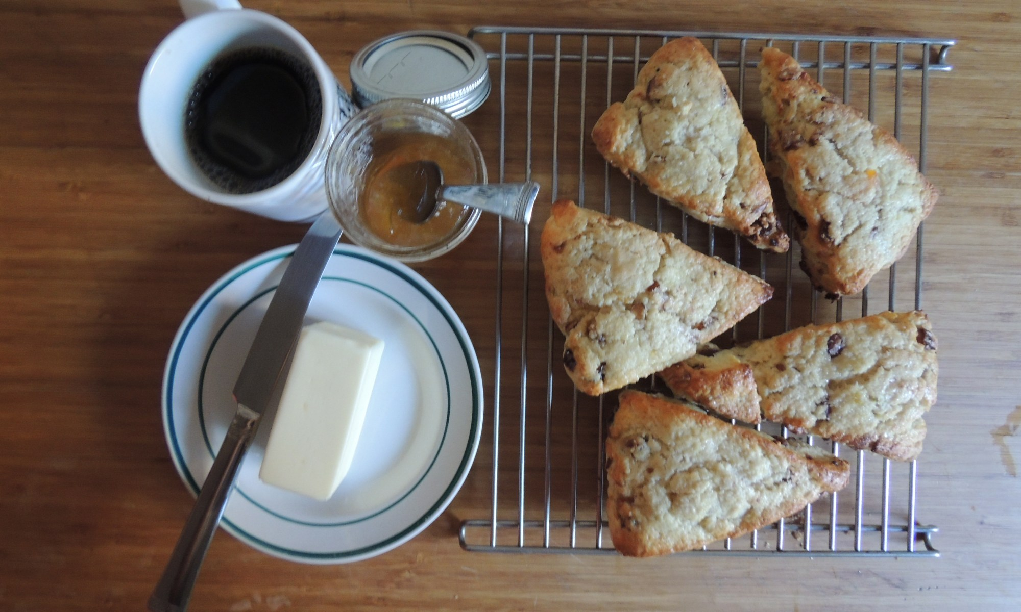 Freshly baked scones with butter. jam and a hot cup of coffee