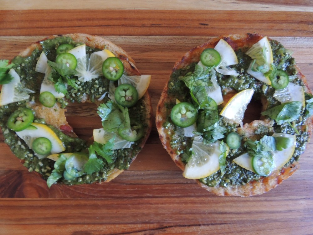 Bagel with lemons, cilantro, basil pesto, and serrano chili