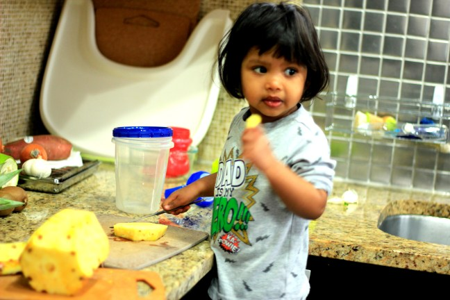 Asha in the kitchen eating pineapple