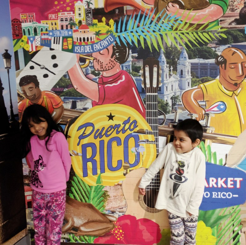 Asha and Arjun standing next to the Puerto Rico Mural