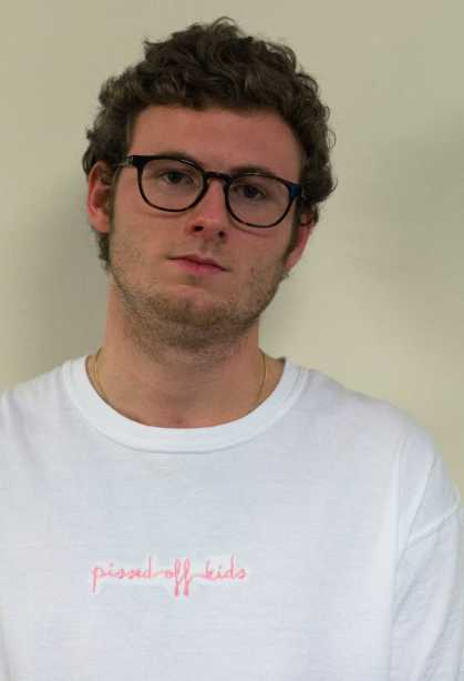 Senior communication/journalism major Hunter Greer wears a white Pissed Off Kids t-shirt. Pissed Off Kids t-shirts come in white, pink, blue and black, all with pink stitching. Photo by Dallas Linger, photo editor.