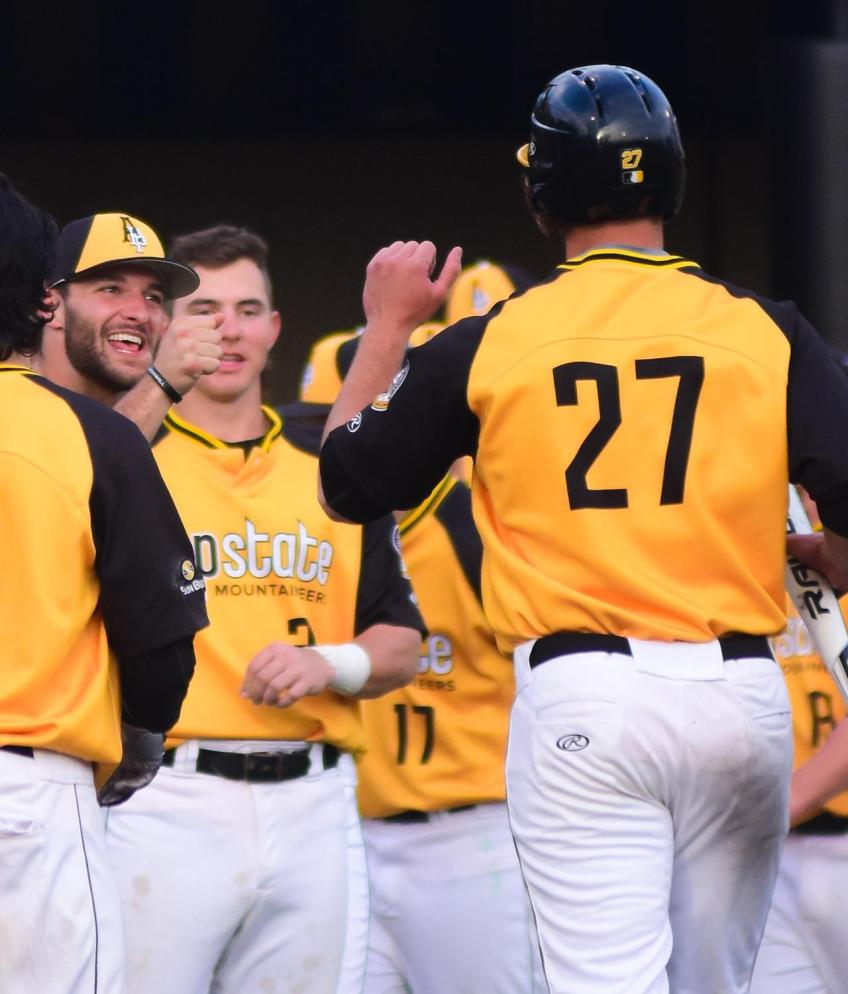 Senior infielder Grayson Atwood returns to the dugout and celebrates with senior right-handed pitcher and infielder Caleb McCann after making a run to home plate. Photo by Dallas Linger, Photo Editor