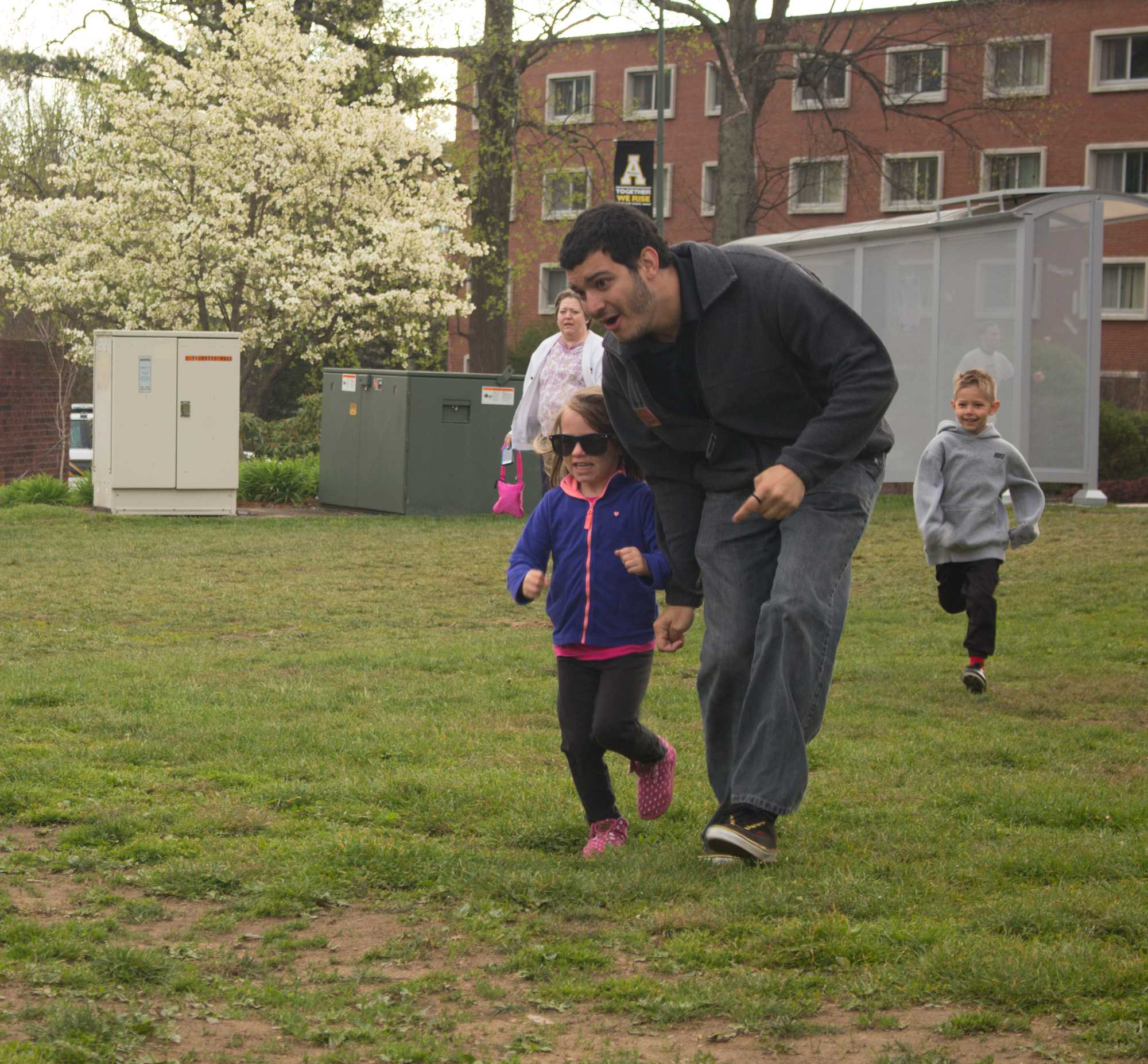 Freshman Brazilian international student Artese Murilo helps a young girl cross the finish line. Photo by Aaron Moran.