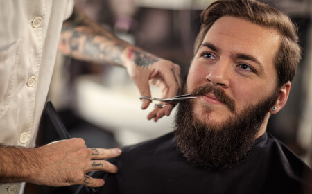 Man trimming beard using scissor