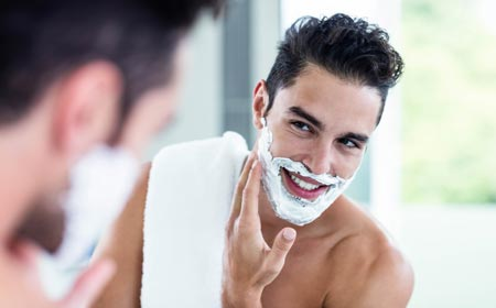 Man preparing for shave using shaving cream.