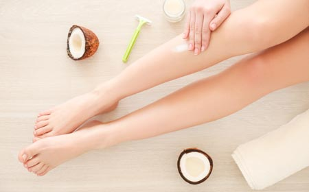 women using coconut oil for getting rid of strawberry legs