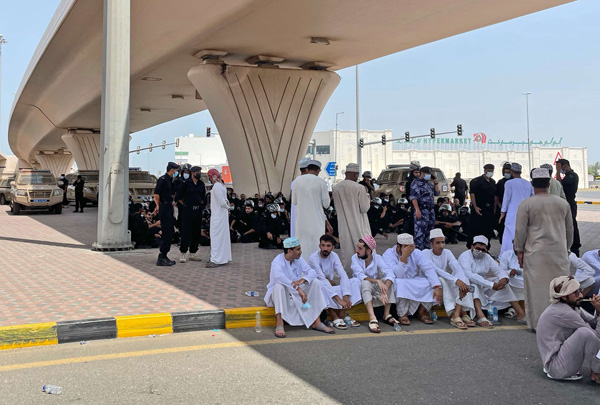 People and security forces talk under a bridge, in Sohar, Oman, May 25, 2021. (AP)