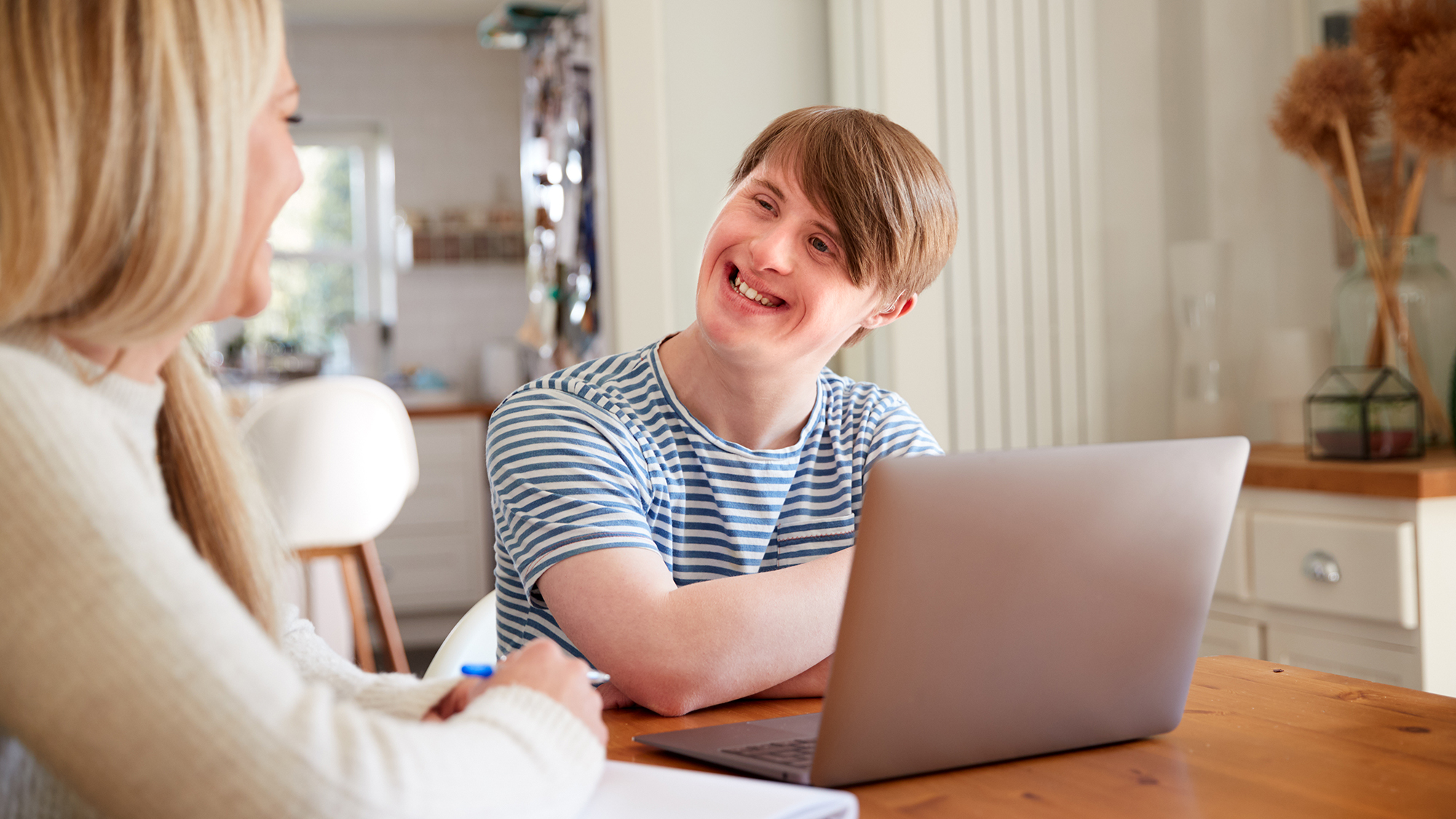 Downs Syndrome Man Sitting With Home Tutor Using Laptop For Lesson At Home