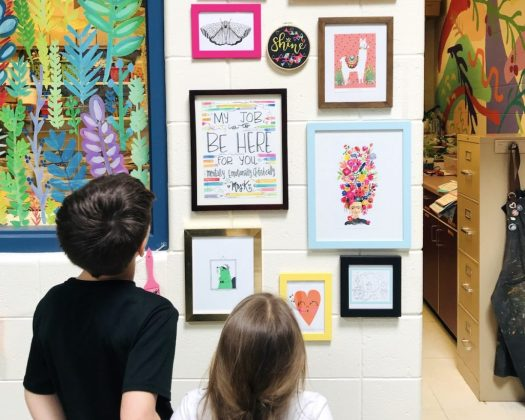 students looking at classroom gallery wall