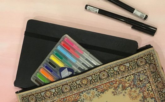 Image of sketchbook and pens in a small purse