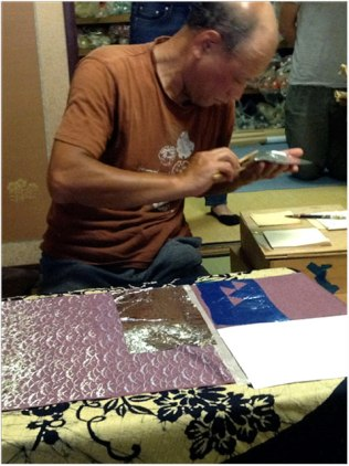 Applying the gold. Two kinds of stenciling can be seen – a precut stencil pattern that can be repeated indefinitely (the arcs) and a blue stencil cut free-hand directly on the fabric (triangles).