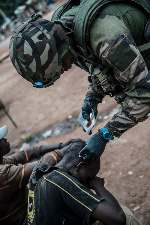09  decembre 2013, 11h38, dans l'axe principal de BANGUI, lors de la mission de désarmement de la SELEKA, un personnel du 1° Regiment de chasseurs parachutistes de Pamiers  effectue un soin sur un habitants de BANGUIS aprés avoir étés percuter par un vehicule de la SELEKA aprés un tic sur la position juillet 14.
