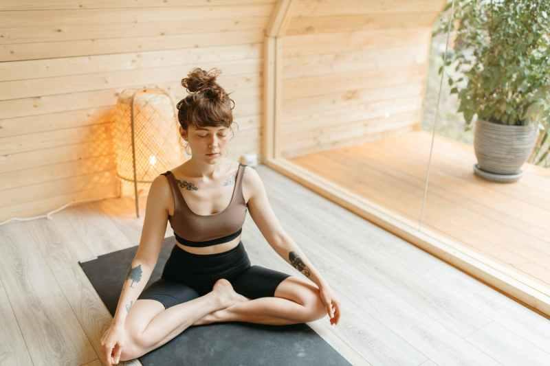 tattooed woman in activewear meditating