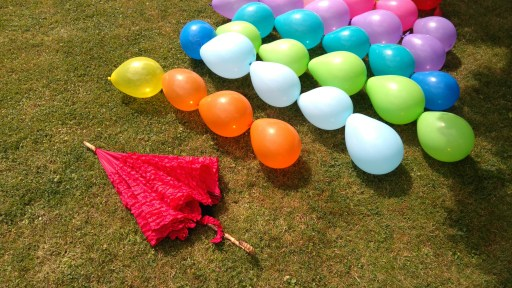 strands of balloons and an umbrella ready to build a garden party balloon den
