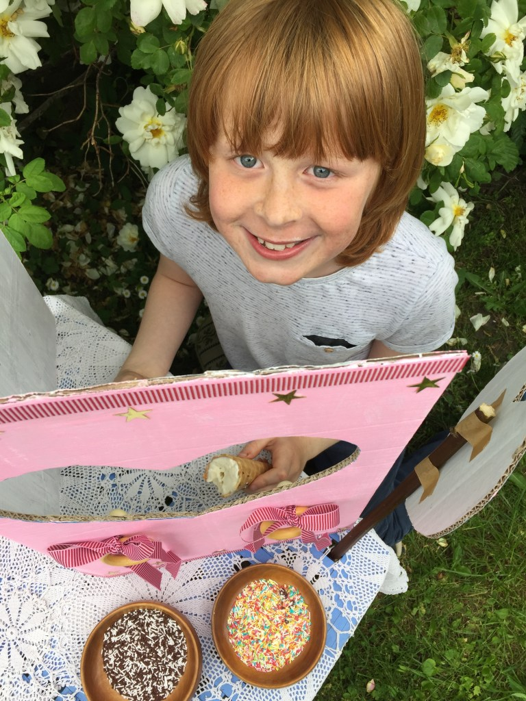 a great handmade summer party craft - make a cardboard box ice cream party stall! a boy sitting in na ice cream stall with ice cream cornets