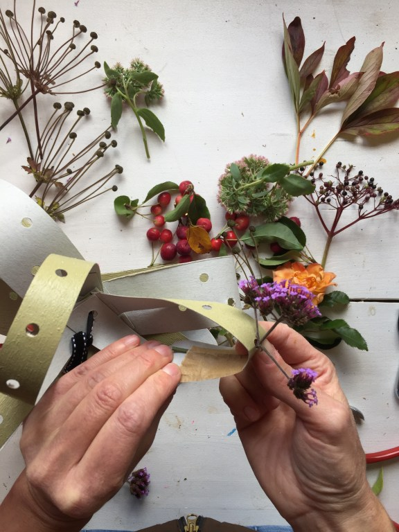 attach the stems of your foliage to the back of the fascinator card strips with tape