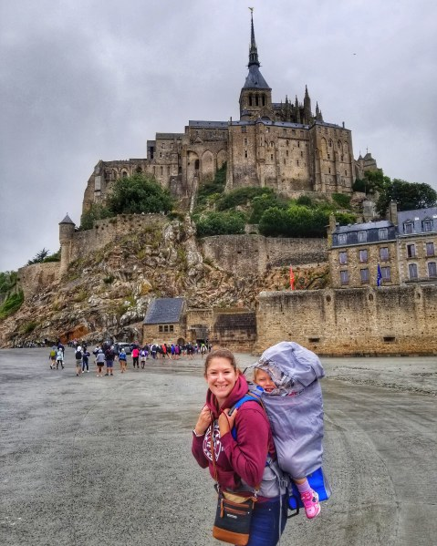 Me and My Daughter Outside Mont Saint-Michel with my backpack carrier with the rain jacket covering on.