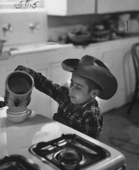 vintage photograph of young cowboy with cowboy hat pouring coffee from a metal pot on top. Making Cowboy coffee