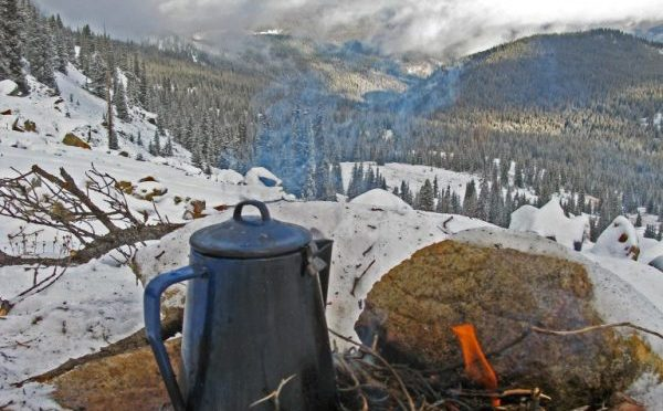 cooking cowboy coffee in enamel coffee pot on a campfire in the colorado high country while elk hunting in the snow