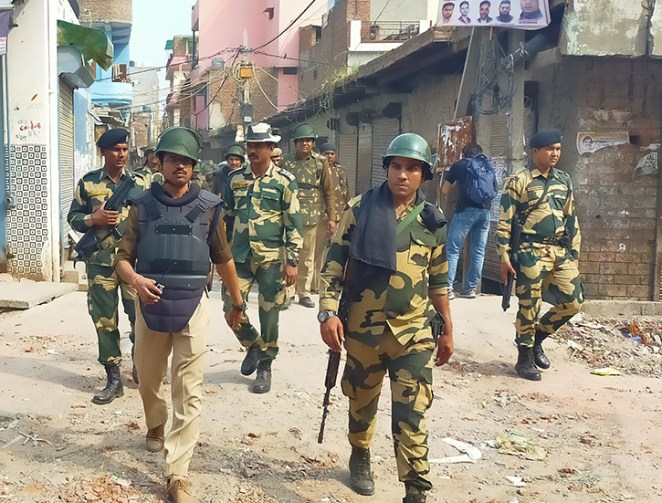 Photograph of Indian police walking through a neighborhood in Delhi