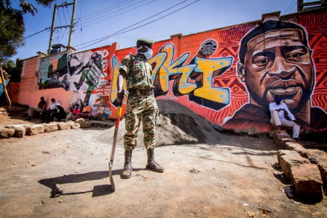 A National Youth Service officer is seen standing close by a painting mural representing police brutality.