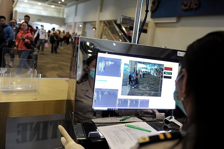 Officers monitor the body temperature of passengers using a body temperature scanner at the International Arrival Terminal I Gusti Ngurah Rai International Airport, Bali