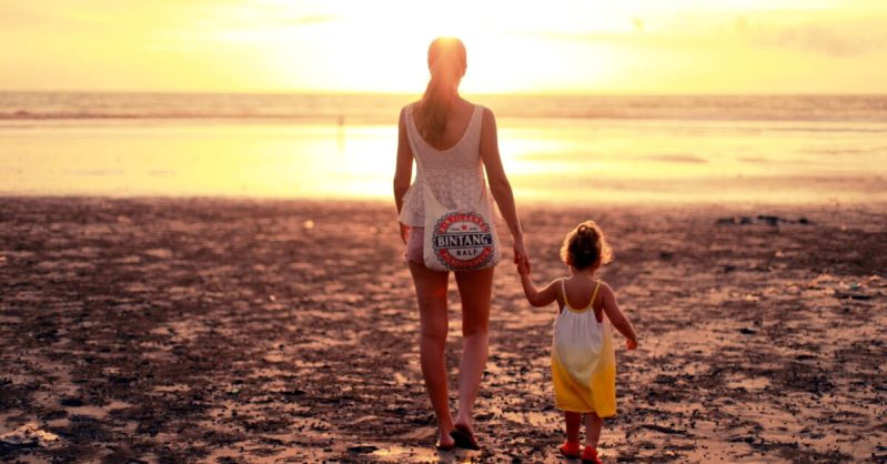 Woman Holding Hands With Toddler At The Beach