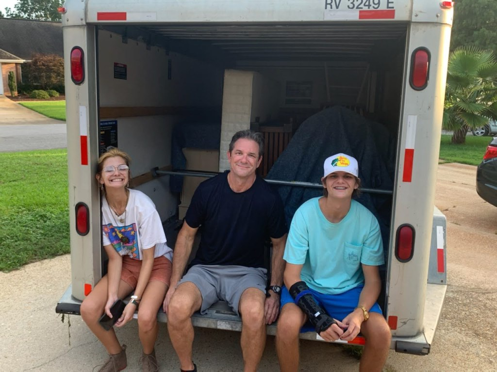 A Dad &Amp; His Son And Daughter Sit On A Uhaul, Smiling.