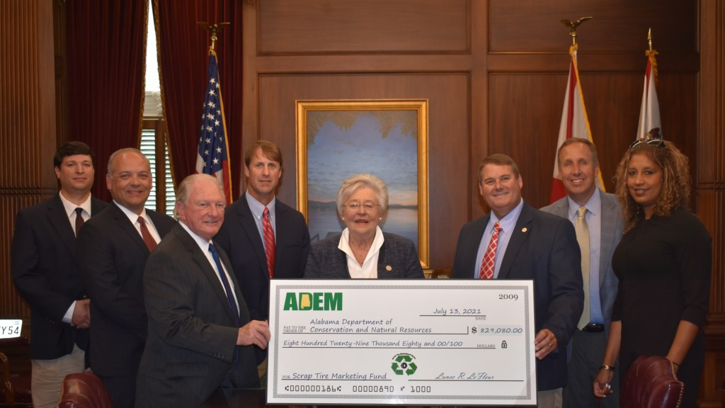 Gov. Kay Ivey Standing With The Dept Of Conservation Holding A Check.