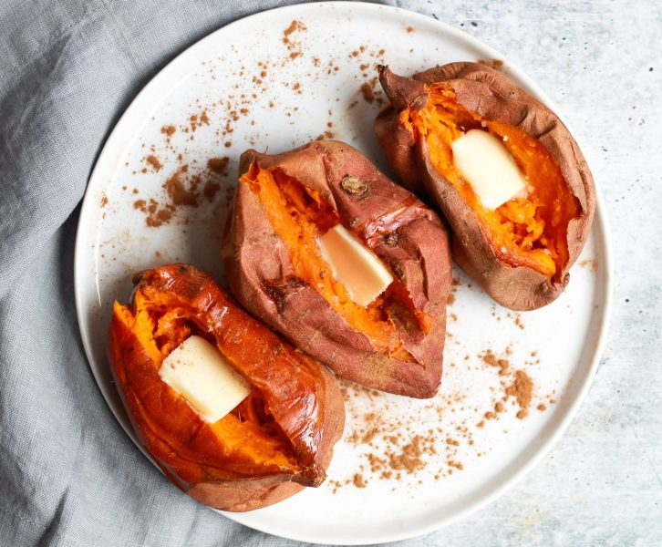 overhead view of three baked sweet potatoes with a pat of butter in them each