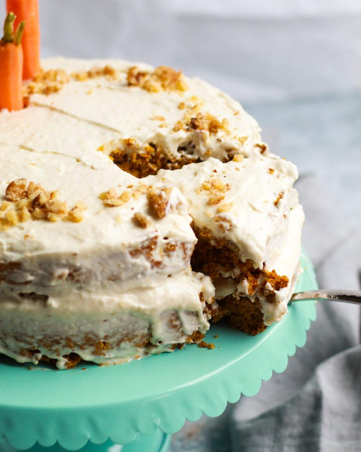 slice of vegan carrot cake being pulled out of full cake