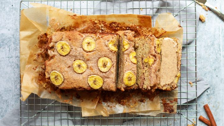 paleo cinnamon swirl almond bread with a slice smeared in almond butter on a drying rack