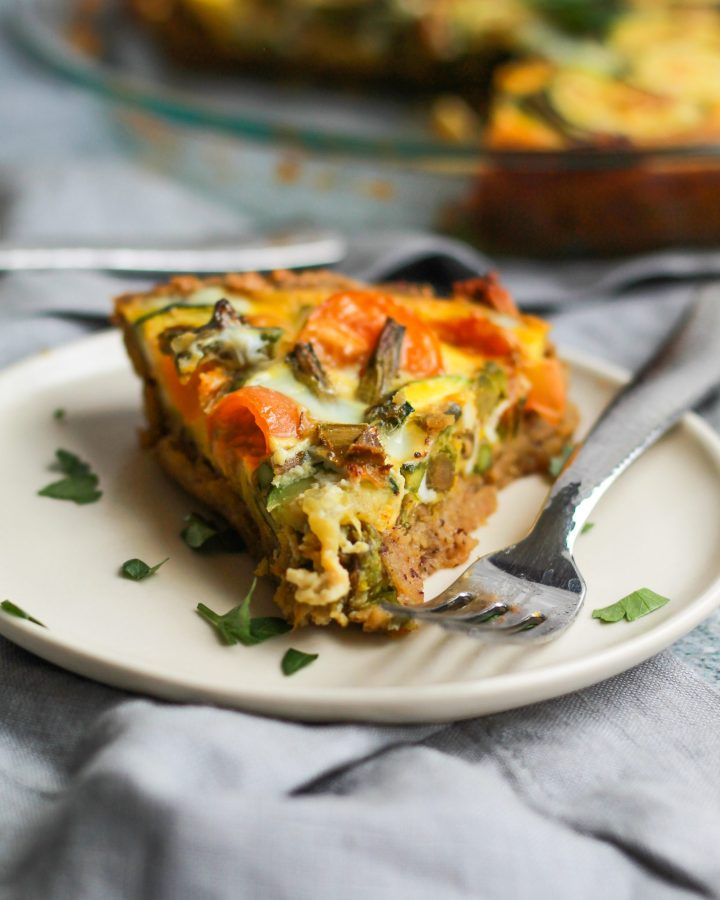 slice of paleo quiche lorraine on a plate with parsley