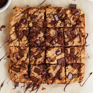 chocolate chip blondies drizzled in chocolate on parchment paper