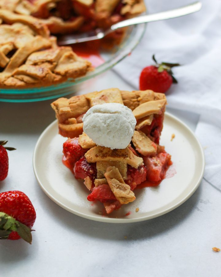 front view of strawberry rhubarb pie with scoop of ice cream on top