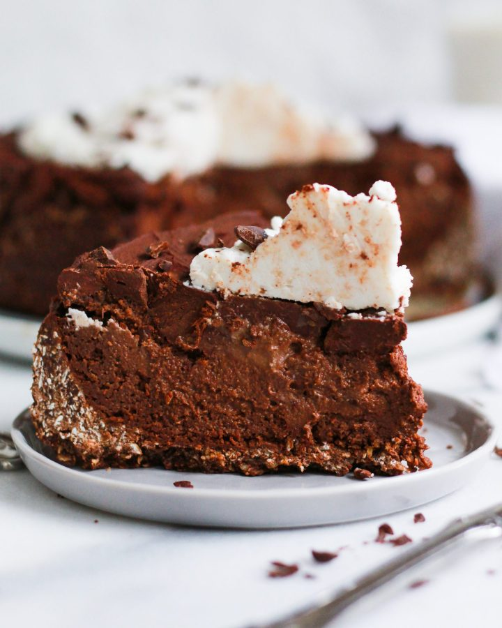 slice of baked vegan chocolate cheesecake with coconut cream