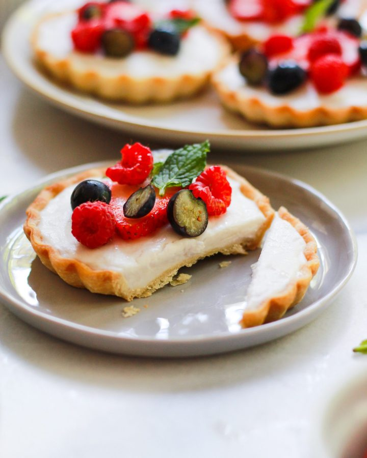 sliced vegan mini fruit tart with custard and berries