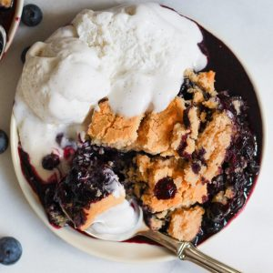 plate of vegan blueberry cobbler with coconut milk ice cream