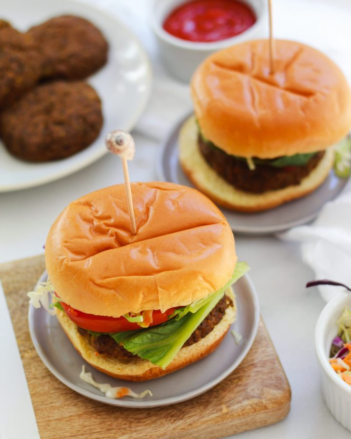 veggie burgers with toothpicks on a wooden board